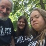 Three Caucasian people wearing black ADA 30 t-shirts smile for a group photo.