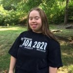A Caucasian person in a black ADA 30 t-shirt smiles for a picture.
