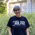 A person in a black ADA 30 t-shirt takes a picture.