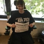 A Caucasian person seated in a wheelchair wearing a black ADA 30 t-shirt holds a sign that reads AN ACCESSIBLE WORLD IS INCLUSIVE FOR ALL PEOPLE!