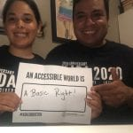 A pair of people wearing black ADA 30 t-shirts hold a sign that reads AN ACCESSIBLE WORLD IS A BASIC RIGHT!