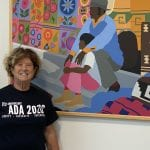 A Caucasian person wearing a black ADA 30 t-shirt stands next to a colorful mural.