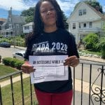 A person wearing a black ADA 30 t-shirt holds a sign that reads AN ACCESSIBLE WORLD IS FOR EVERYONE NO MATTER WHO YOUR ARE!!!