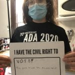 A Caucasian person wearing a black ADA 30 t-shirt and blue facial mask holds up a sign saying I HAVE THE CIVIL RIGHT TO VOTE! THE POLLS MUST BE ACCESSIBLE.
