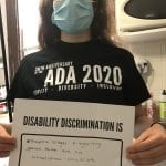 A person wearing a black ADA 30 t-shirt and blue face mask holds up a sign saying DISABILITY DISCRIMINATION THEATRE STAGES & ORGANIZING SPACES THAT ARE NOT WHEELCHAIR ACCESSIBLE.