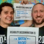 Two Caucasian people wearing black ADA 30 t-shirts hold signs that read AN ACCESSIBLE WORLD INCLUDES OPPORTUNITIES FOR ALL and DISABILITY DISCRIMINATION IS NARROW MINDED.