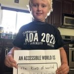 A Caucasian child wearing a black ADA 30 t-shirt holds a sign that reads AN ACCESSIBLE WORLD IS THE KIND OF WORLD I WANT TO HELP MAKE.