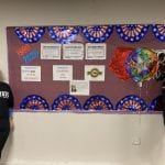 Two people wearing black ADA 30 t-shirts stand next to a bulletin board decorated for the ADA event.