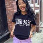 An Asian person wearing a black ADA 30 t-shirt.