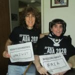 Two Caucasian people, one in a wheelchair, wearing black ADA 30 t-shirts hold signs that read AN ACCESSIBLE WORLD IS FAIR and DISABILITY DISCRIMINATION IS UNJUST.