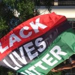 A flag consisting of three horizontal lines, one red, one black and one green, reads BLACK LIVES MATTER in large white letters.