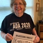 A Caucasian person wearing a black ADA 30 t-shirt holds a sign that read AN ACCESSIBLE WORLD IS INCLUSIVE.