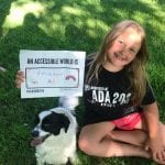 A Caucasian child sitting with a dog and wearing a black ADA 30 t-shirt holds a sign that reads AN ACCESSIBLE WORLD FREEDOM FOR ALL.