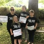 Four people, three of them children, smile for a group photo wearing black 30 ADA t-shirts and holding up signs.