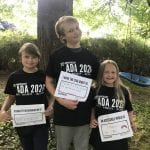Three children smile for a group photo wearing black 30 ADA t-shirts and holding signs.