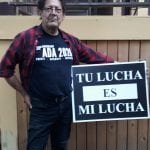 A Caucasian person wearing a black ADA 30 t-shirt holds up a sign that reads TU LUCHA ES MI LUCHA (Your fight is my fight).