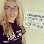 A Caucasian person wearing a black ADA 30 t-shirt holds a sign that read AN ACCESSIBLE WORLD IS BRAILLE AND LARGE PRINT OPTIONS EVERYWHERE! i.e. - RESTAURANTS, SIGNS, BOOKS, etc.