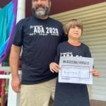 A Caucasian person and child wearing a black ADA 30 t-shirts hold a sign that reads AN ACCESSIBLE WORLD IS A WORLD WITHOUT BARRIERS!