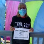 A Caucasian person wearing a black ADA 30 t-shirt and blue face mask holds up a sign saying DISABILITY DISCRIMINATION IS UNKIND. KINDNESS MATTERS.