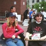 Two people seated in wheelchairs smile for a photo.