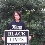 A Caucasian person holds up a sign that reads Black Lives Matter.