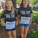 Two Caucasian children wearing black ADA 30 t-shirts smile for a photo holding signs.