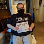 A Caucasian person sitting in a wheelchair, wearing a black ADA 30 t-shirt and mask, holds up a sign saying I HAVE THE CIVIL RIGHT TO VOTE!