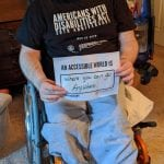 A Caucasian person wearing a black ADA 30 t-shirt and face mask sits in a wheelchair holds a sign that read AN ACCESSIBLE WORLD IS WHERE YOU CAN GO ANYWHERE.
