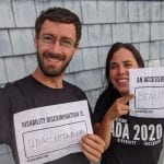 Two Caucasian people wearing black ADA 30 t-shirts hold signs that read AN ACCESSIBLE WORLD IS BEAUTIFUL and DISABILITY DISCRIMINATION IS UNACCEPTABLE.