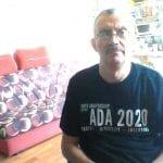 A Caucasian person wearing a black ADA 30 t-shirt takes a photo.