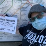 A person sitting in a wheelchair, wearing a black ADA 30 t-shirt and blue face mask, holds up a sign saying I HAVE THE CIVIL RIGHT TO RIDE PUBLIC TRANSIT WHENEVER I WANT TO! in front of a map of the MBTA subway lines.