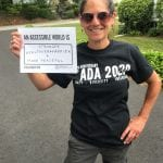 A Caucasian person wearing a black ADA 30 t-shirt holds a sign that reads AN ACCESSIBLE WORLD IS STRONGER, HEALTHIER, HAPPIER + MORE PEACEFUL.