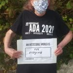 A person wearing a black ADA 30 t-shirt holds a sign that reads AN ACCESSIBLE WORLD IS FOR EVERYONE.