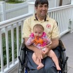 A Caucasian person seated in a wheelchair takes a picture with a baby in their lap.