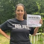 A Caucasian person wearing a black ADA 30 t-shirt holds up a sign saying I HAVE THE CIVIL RIGHT TO VOTE.