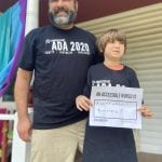 An adult and child wearing a black ADA 30 t-shirts hold a sign that reads AN ACCESSIBLE WORLD IS A WORLD WITHOUT BARRIERS!