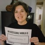 A Caucasian person in a black ADA 30 t-shirt holds up a sign saying AN ACCESSIBLE WORLD IS ACHIEVABLE!!!