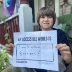 A Caucasian child wearing a black ADA 30 t-shirt holds a sign that reads AN ACCESSIBLE WORLD IS A WORLD WITHOUT BARRIERS!