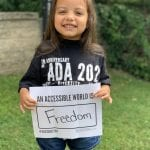 A Caucasian child wearing a black ADA 30 t-shirt holds a sign that reads AN ACCESSIBLE WORLD IS FREEDOM.