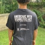 A person wearing a black ADA 30 t-shirt displays the back of the shirt. Text reads AMERICANS WITH DISABILITIES ACT 30TH ANNIVERSARY -JULY 22ND 2020-