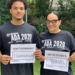 Two people wearing black ADA 30 t-shirts hold up signs saying I HAVE THE CIVIL RIGHT TO TRAVEL and DISABILITY DISCRIMINATION IS UNACCEPTABLE.