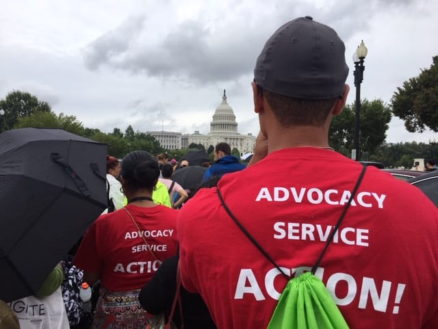A large crowd of people gather outside the U.S. Capitol. In the photo's foreground, two people wear red t-shirts that say ADVOCACY SERVICE ACTION! on the back. A person holds a black umbrella off to the left.